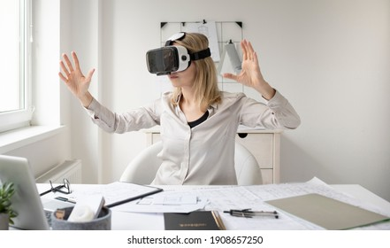 beautiful young female architect with virtual reality goggles in her office