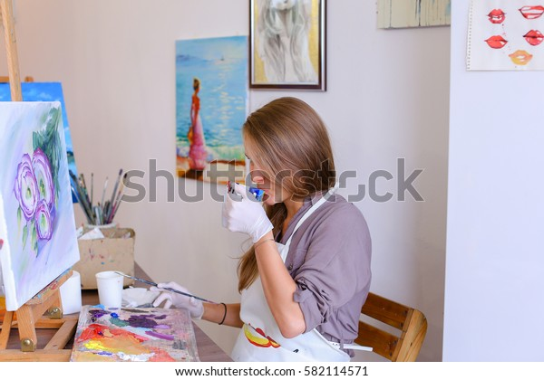 Beautiful young female artist writes and evaluates oil painting, enjoying favorite work and drinking tea. Girl of European appearance draws flower on white canvas. Woman With Long Light Brown Hair