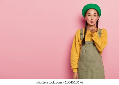 Beautiful young female with Asian appearance, blows air kiss, keeps lips rounded, wears makeup, expresses love to someone, wears fashionable clothes, isolated on pink studio wall. Body language