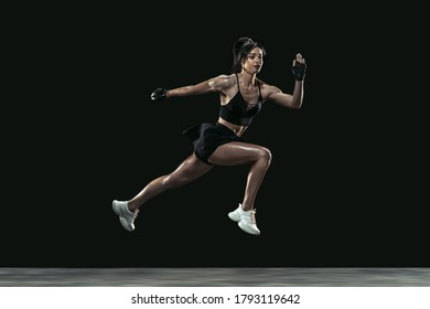 Beautiful young female athlete practicing on black studio background, full length portrait. Sportive fit brunette model in run, jump. Body building, healthy lifestyle, beauty and action concept.