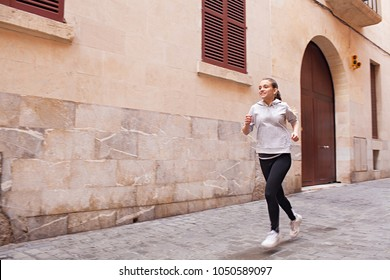 Beautiful young female athlete running in city street working out cardio vascular training outdoors. Sport fitness discipline. Teenager woman exercising jogging, healthy leisure recreation lifestyle.