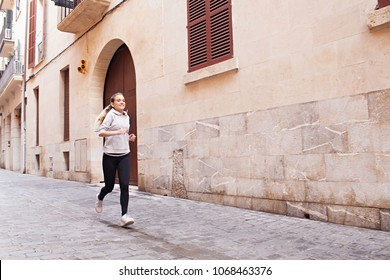 Beautiful young female athlete running in city street working out cardio vascular training outdoors. Sport fitness. Smiling teenager woman exercising jogging, healthy leisure recreation lifestyle.