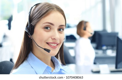 Beautiful young female call center operator with headset in office.