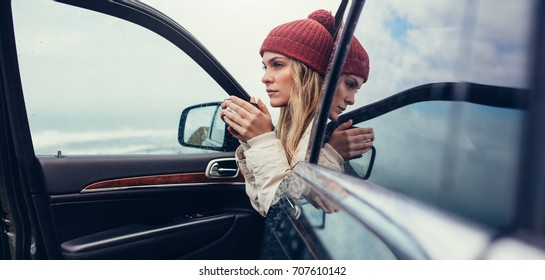 Beautiful young female with coffee in hand sitting in a car. Female on road trip drinking coffee inside car.