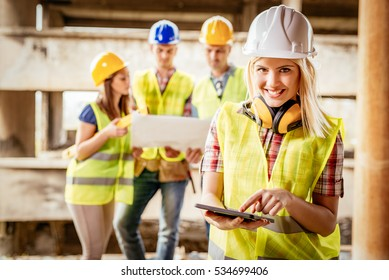 Beautiful young female construction architects using digital tablet at a construction site. Her colleagues review plan in background.