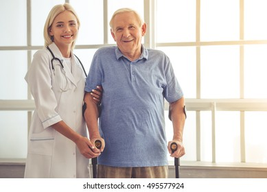 Beautiful young female doctor is helping handsome old man with crutches. Both are looking at camera and smiling