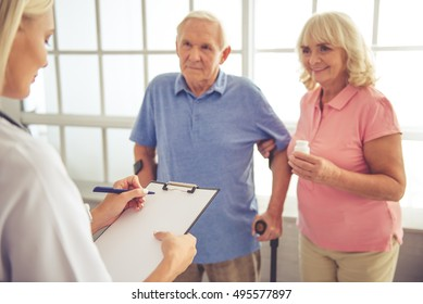 Beautiful young female doctor is talking to old couple and making notes