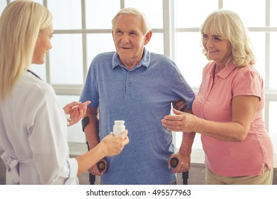 Beautiful young female doctor is talking to old couple and holding a bottle of medicine