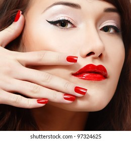 beautiful young female face with vivid red lipstick and nail polish closeup