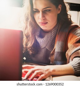Beautiful young female freelancer using laptop  in a cafe at the table. Woman working remotely  online.