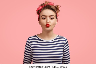 Beautiful young female gives kiss at camera, shows brightly red lips, has make up, wears retro style clothing, poses against pink background. Charming pinup girl in striped sweater flirts with someone