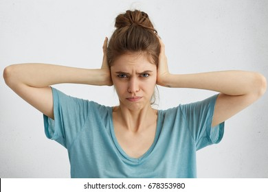 Beautiful young female with hair knot having discontent look plugging her ears being annoyed with noise wanting silence and calm atmosphere being exhausted of loud sound and shouting around her