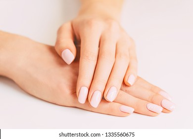 Beautiful young female hands with stylish manicure, nails of pastel pink color. Concept of beauty salon.
