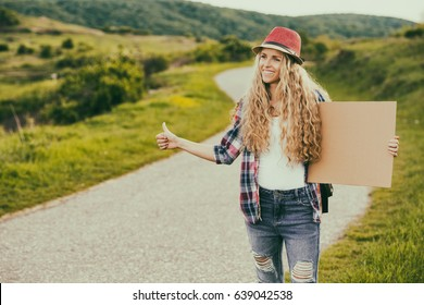 Beautiful young female holding blank cardboard and hitchhiking at the country road.Woman hitchhiking at the countryside Image is intentionally toned.