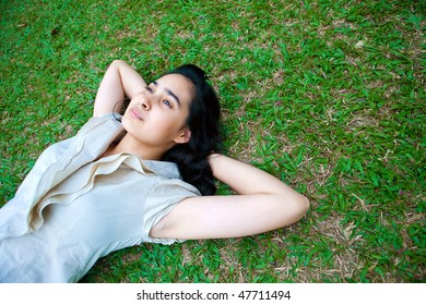 Beautiful young female laying on the grass, thinking