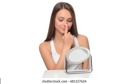 Beautiful young female looking  in the mirror and touching her face