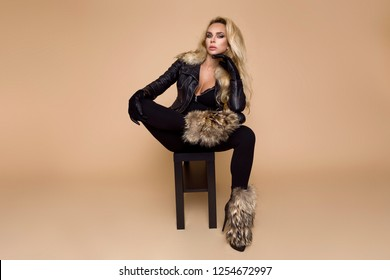 Beautiful, young female model in a autumn-winter clothing, leather jacket and boots on a beige background in the studio. Blonde in elegant biker style clothing