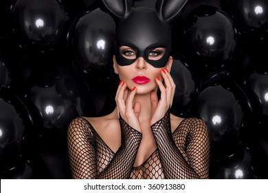 beautiful young female model in a black carnival mask, rabbit ears standing against the black balloons and sensually looks at the camera, wearing bodystocking dress with mesh and amazing makeup