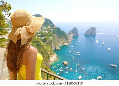 Beautiful young female model with straw hat in Capri Island with Faraglioni sea stack and blue crystalline water on the background, Capri, Italy