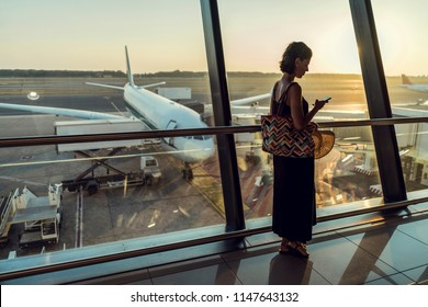 Beautiful young female on airport. Woman waiting for her airplane and using mobile phone. Flight application using to check in
