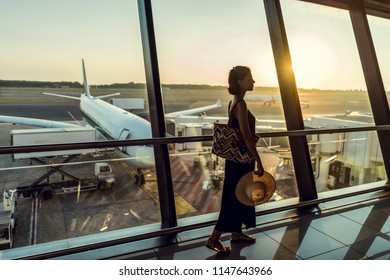 Beautiful young female on airport. Woman waiting for her airplane and looking through window.