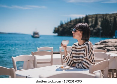 Beautiful young female on holidays drinking coffee at cafe next to sea with beautiful view