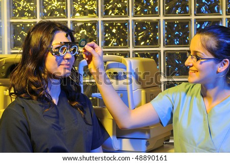 989d8acfac0 Beautiful young female patient having a medical examination at optician - a  series of dramatically lightened