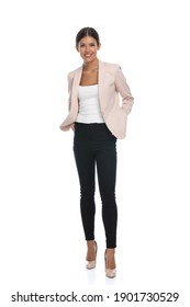 beautiful young female in pink jacket holding hands in pockets and smiling, standing and posing on white background in studio, full body