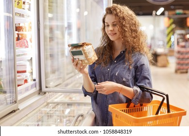 Beautiful young female with pleased expression, holds shopping cart, reads information abpput product, stands near fridge in supermarket, chooses necessary items for preparing delicious dinner
