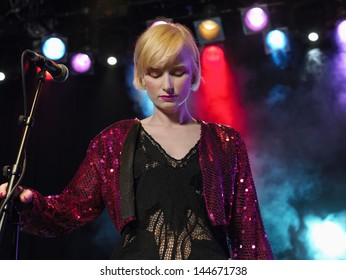 Beautiful young female singer standing with eyes closed by microphone on stage in concert