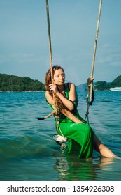 Beautiful young female sitting on the swing on sea shore