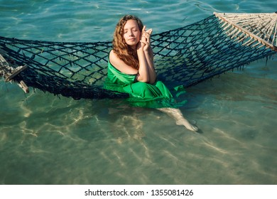 Beautiful young female sitting on the hammock on sea shore