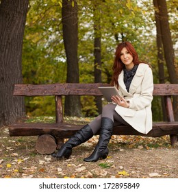 Beautiful young female sitting on tree and smiling, looking into forest with tablet PC in her hand, autumn season.