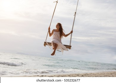 Beautiful young female sitting on the swing on sea shore enjoy summer