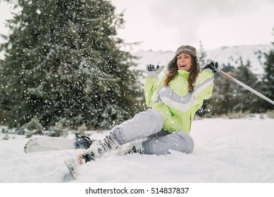 Beautiful young female skier falling down on mountain slope.