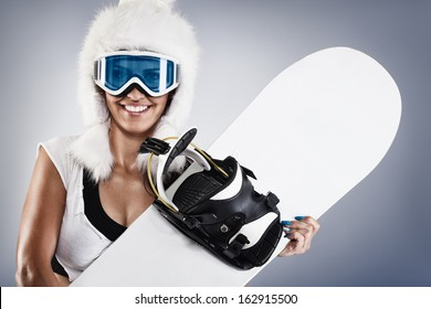 Beautiful young female snowboarder with white fur hat
