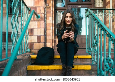 Beautiful young female student with backpack sitting on stairs using phone in the city.