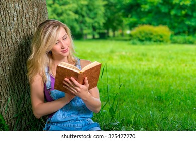 Beautiful young female student with a good book in the park