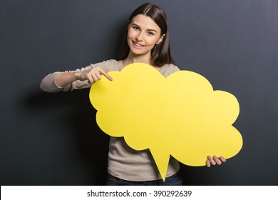 Beautiful young female student is holding a yellow speech bubble, pointing on it and smiling, standing against blackboard