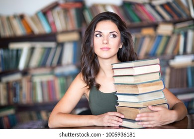 Beautiful young female student sitting on the background of bookshelves in the library