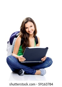 Beautiful young female student sitting on floor studying on a laptop, isolated on white