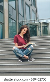 Beautiful young female student sitting on the stairs of the university with a book in her hands and reading