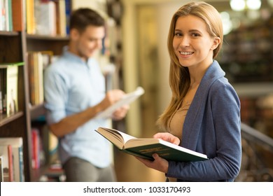 Beautiful young female student smiling to the camera holding a book while studying at the library copyspace education learning smart intelligence confidence achievement assignment project ideas.