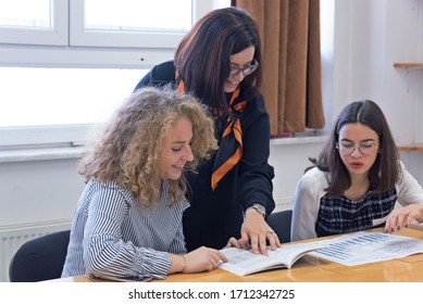 Beautiful young female teacher helping a student during class. Female Professor Holding Lecture to Multi Ethnic Group of Students.