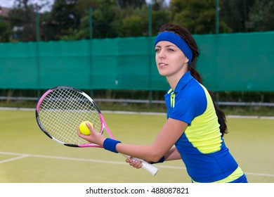 Beautiful young female tennis player serving wearing a sportswear during a tennis match on tennis grass court  outdoor in summer or spring