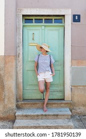 Beautiful young female tourist woman wearing sun hat, standing and relaxing in shade in front of turquoise vinatage wooden door in old Mediterranean town while sightseeing on hot summer day.