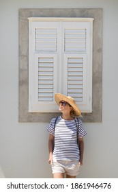 Beautiful young female tourist woman wearing sun hat, standing and relaxing in front of vinatage wooden window in old Mediterranean town while sightseeing on hot summer day.