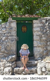 Beautiful young female tourist woman wearing big straw hat using moile phone, sitting in front of white vinatage wooden door and textured stone wall at old Mediterranean town.