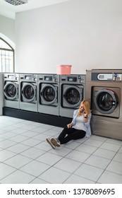 Beautiful young female using phone while waiting at laundromat