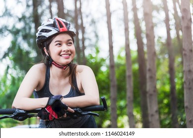Beautiful young female woman helmet activity bicycle at forest on summer with copy space